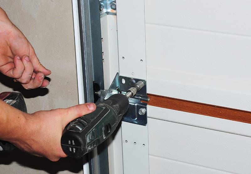 Repairman repairing installing garage door OR
